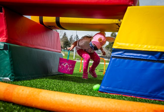 """Adeliene Jarvis, 4, crawls through a tunnel in the first obstacle course to claim the egg on the other side. Eugene Civic Alliance welcomed kids and families to Civic Park for """"Easter Egg-stravaganza,"""" one of the first events at the new park, on Sunday, April 4, 2021."""