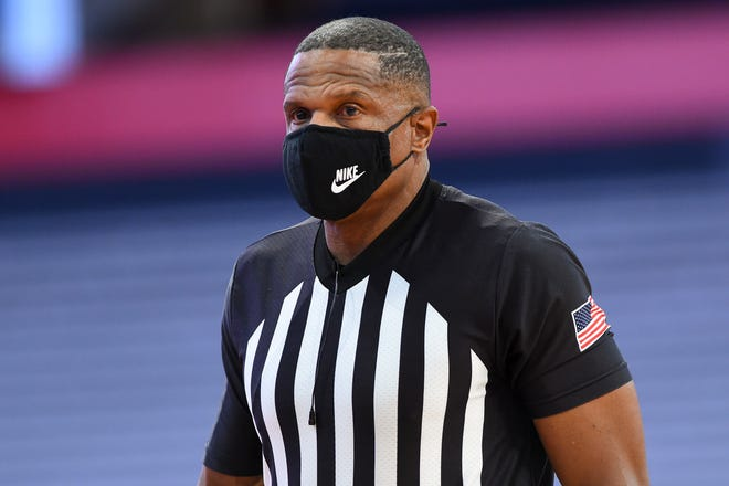 NCAA referee Ted Valentine looks on while wearing a mask during a timeout in the first half of a Jan. 6, 2021, game between Pittsburgh and Syracuse at the Carrier Dome in Syracuse, N.Y.