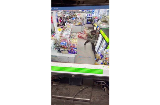 This video provided by Mark Sung shows a man with a pole trashing an Asian-owned convenience store on Tuesday, March 30, 2021 in Charlotte, N.C.  Surveillance footage shows the man pulling a merchandise rack to the floor and swinging a street sign post into the glass on the refrigerators. Charlotte-Mecklenburg Police said a company that's responsible for security at the transit center arrested Xavier Rashee Woody-Silas. He was arrested on charges that include robbery with a dangerous weapon and communicating threats. (Mark Sung/Grace Lee Sung via AP)
