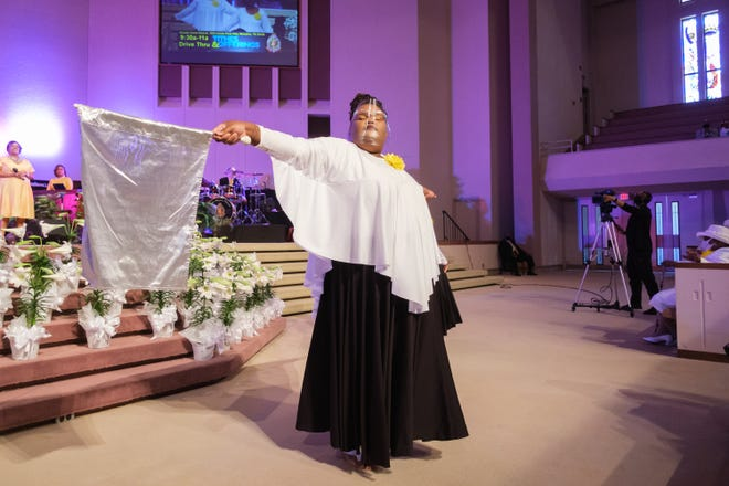 A church member at Greater Imani Church wears a face shield and waves a flag during Easter service, Sunday, April 4, 2021, in Memphis.