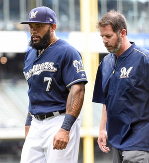 Brewers assistant athletic trainer Dave Yeager, shown here in 2017 with former Milwaukee first baseman Eric Thames, remained hospitalized after a second episode of light-headedness after a game Saturday night against the Twins.