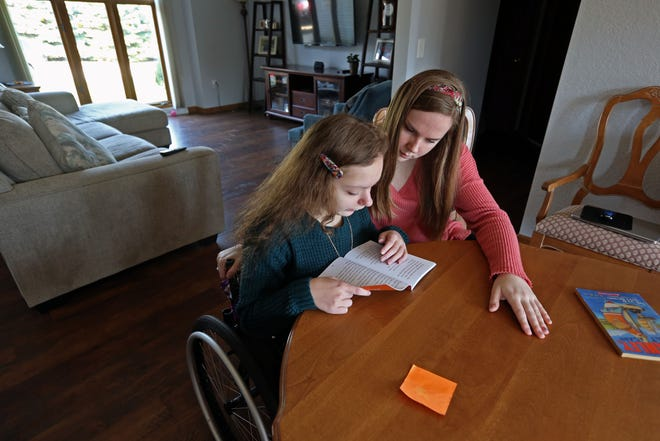 Madison, left, gets help with her school reading from older sister Joanie Kierzek at their Waukesha home. Joanie, a student at UW-Madison, feels not having a spring break has contributed to high levels of burnout. While doing her schoolwork she has also become the primary caregiver of her younger sister, who is immune compromised and in a wheelchair due to spina bifida.