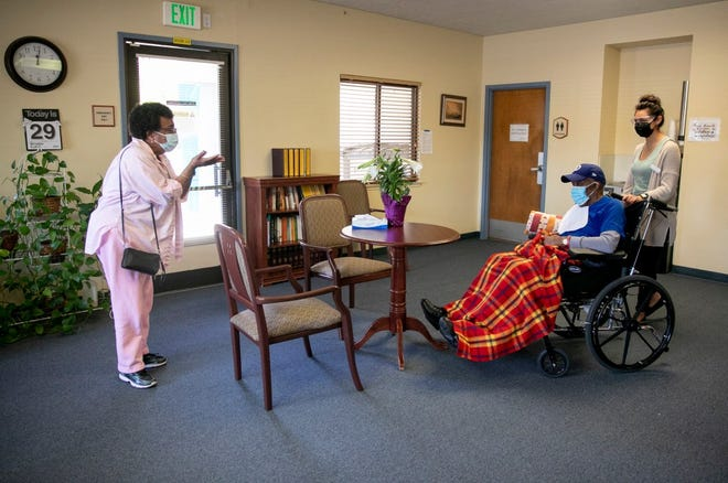 Ouida Dill, left, blows a kiss to her husband, David, at the end of their visit at Lincoln Glen Skilled Nursing Facility in San Jose. David has been a resident at Lincoln Glen for more than four years. For the past year, Ouida visited him almost every day through a window. Now that Ouida is vaccinated, the couple can see each other indoors again.