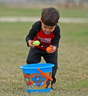 Alijah Torres puts easter eggs in his basket during an event at Sports Next Level on Saturday, April 4, 2021.