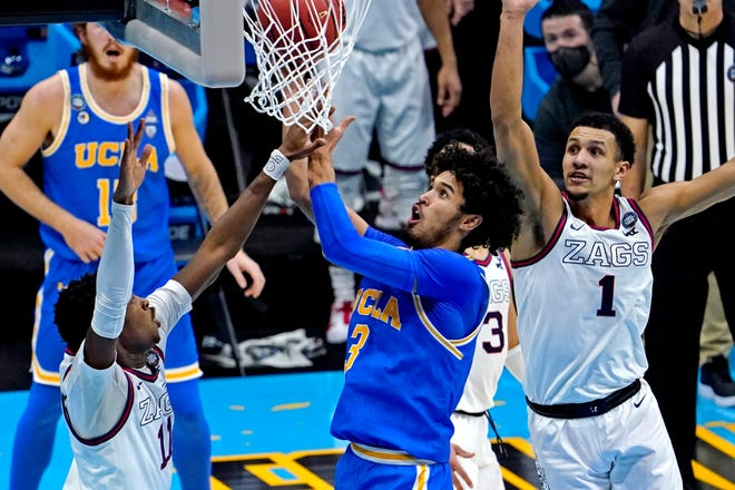 UCLA Bruins guard Johnny Juzang (3) shoots the ball against Gonzaga Bulldogs guard Jalen Suggs (1) and guard Joel Ayayi (11) during the first half in the national semifinals of the Final Four of the 2021 NCAA Tournament at Lucas Oil Stadium.