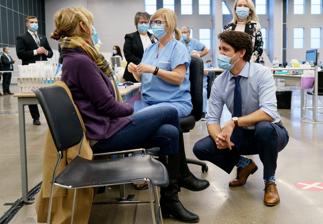 Canada's Prime Minister Justin Trudeau chats with a woman about to receive a COVID-19 vaccine while touring a vaccination clinic in Montreal on Monday, March 15, 2021.