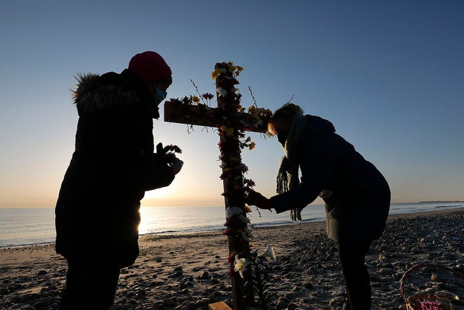 Maureen Ferguson and Betsey Hunter place flowers on the cross as a sign of rebirth and renewal during the Pilgrim Church of Duxbury Easter sunrise service on Duxbury Beach, Mass. Sunday, April 4, 2021.