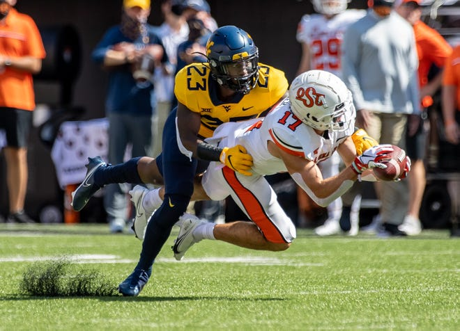Sep 26, 2020; Stillwater, Oklahoma, USA; Oklahoma State Cowboys wide receiver Dillon Stoner (17) reaches for a pass while defended by West Virginia Mountaineers punter Tykee Smith (23) during the first half  at Boone Pickens Stadium. Rob Ferguson-USA TODAY Sports