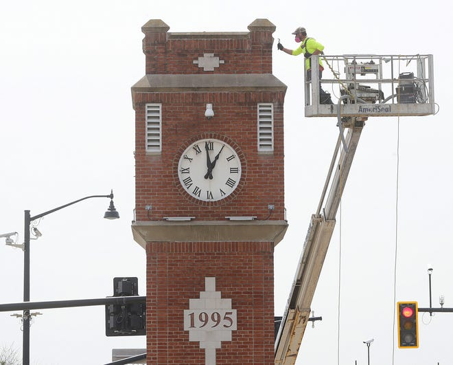 Chase Owens of AmeriSeal works on the restoration of the clock tower on Front Street on Monday, April 5, in Cuyahoga Falls.  The preventive maintenance includes replacing a number bricks with donors' names, tuckpointing and replacing the seal around the clock faces. [Phil Masturzo/ Beacon Journal]