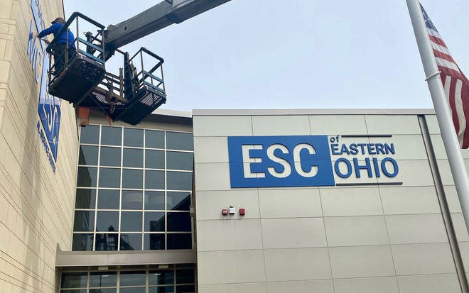 Workers change the signs on the Canfield office after Mahoning County Educational Service Center announced has changed its name to Educational Service Center of Eastern Ohio.
