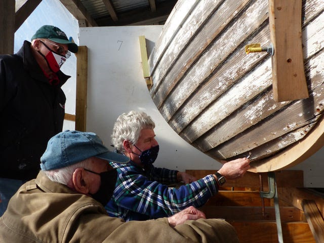 Volunteers Peter Cross (standing, left), Richard Boonisar (kneeling) and William Stirling (right) examine the surfboat's condition after new keel has been fitted.