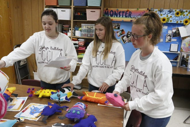 """Freshmen (from left) McKenna Cash, Avery Dozier and Bethany Blair describe how they used small """"monsters"""" to teach hygiene skills to Zephyr first-grade students."""