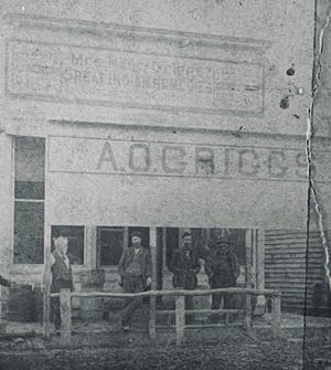 """Courtesy of the Butler County Historical Society Home of the Kansas Oil Museum AO Griggs Grocery 1883 A large sign above A.O. Griggs Grocery store advertises """"Mrs. Nancy Griggs Great Indian Remedies,"""" circa 1883."""