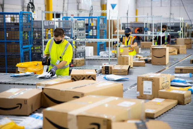 Amazon workers sort packages.