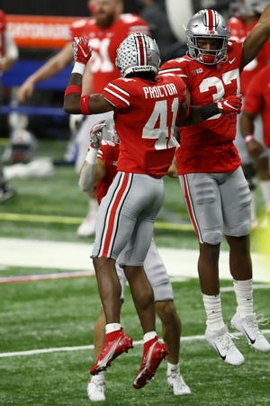 Ohio State linebacker Mitchel Melton, right, celebrates with safety Josh Proctor after Proctor intercepted a pass against the Northwestern on Dec. 19.
