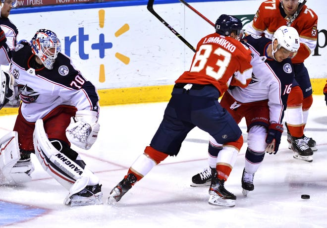 Blue Jackets goalie Joonas Korpisalo looks over as Max Domi tries to clear the puck from the front of the net while being checked by the Panthers' Juho Lammikko on Sunday.