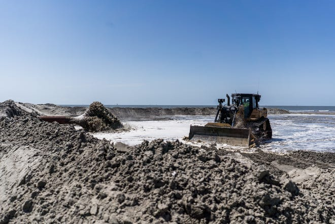 Bulldozers push dredged sediment into place Monday along Trinity-East Island as part of a project to restore the eroded barrier island off Terrebonne Parish.