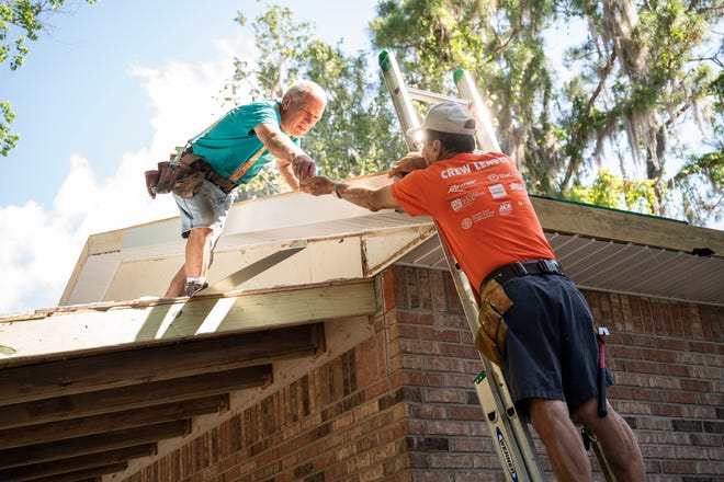Volunteers from Habitat for Humanity work on repairing siding on the roof at the home in Leesburg.