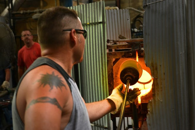 Glass is put into the furnace to be reheated.