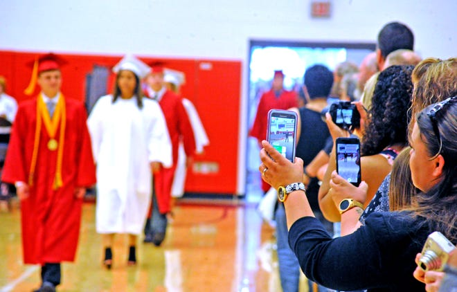 Parents and family members captured Orrville High School graduates on their phones and cameras as they entered the gymnasium on graduation day. (File photo)