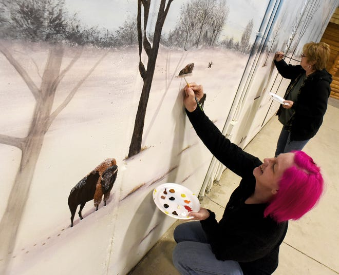"""Volunteer Brandy Gerber, at left, finishes painting a bison, while Darlene Belair finishes around a tree as the two near completion of a 52-by-14 feet winter scene mural inside the Education Center at the River Raisin National Battlefield. """"This mural is a teaching wall,"""" said Belair. There are different type of tress such as black walnut, sugar maples and more, along with different animals. """"We will paint the same trees on the other three seasons, spring, summer and fall murals,"""" added Gerber. The spring scene will be located near the entrance and the winter scene will be near the end of the experience."""