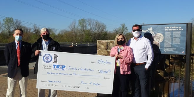The Tourism Recreation Investment Partnership in Davidson County recently received a $150,000 contribution for improvements to Yadkin River Park. Pictured are Ronnie Smith (right), Friends of Rowan; Davidson County Commissioners Steve Shell and Karen Watford; and Chris Phelps, executive director of TRIP.