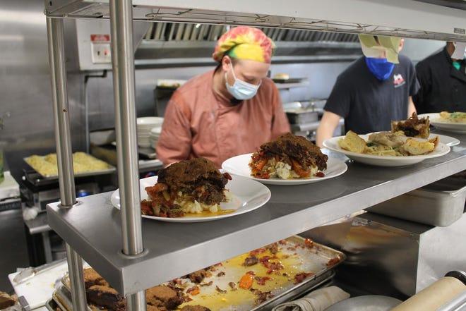 Executive Chef Colin Ferington (left) preparing braised beef short rib and pork loin.
