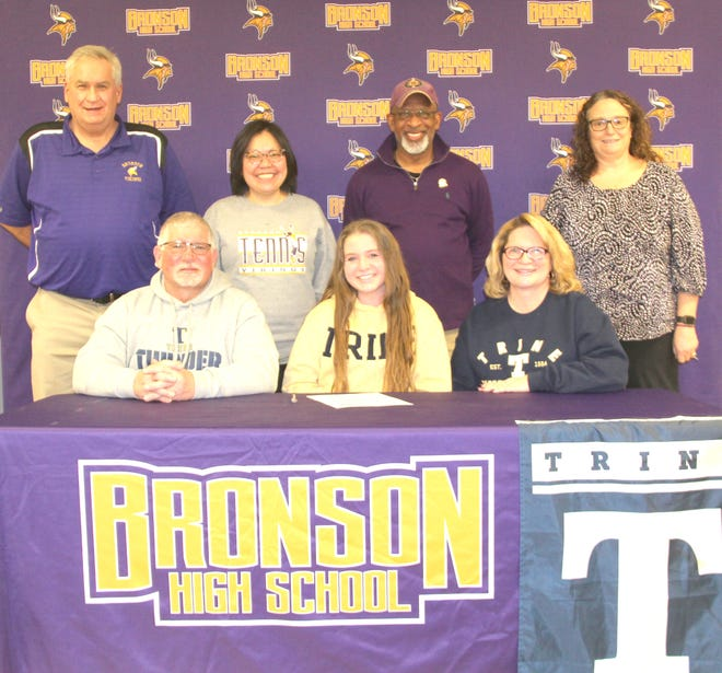 Bronson's Kennedy Outwater, joined her by family and coaches, recently signed her letter of intent to play tennis at Trine University.