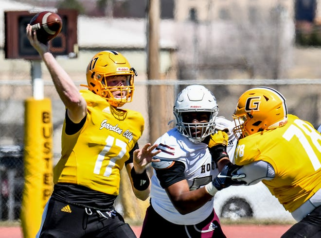 Garden City Community College quarterback Devin Larsen, left, throws a pas to a receiver as Isaiah Adams, right, provides protection Saturday against Fort Scott at Broncbuster Stadium. The Broncbusters set a new all-time scoring record n the game with 76 points.