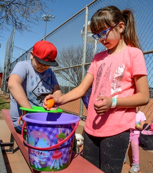 Marijose Hernandez, 8, and her brother, Julian, 10, sort through the plastic eggs they collected to see what candy they got Saturday after the GCRC's Easter egg hunt at Deane Wiley Park.