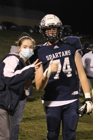 Ball Girl Lauren Anderson and Lineman Brant Casteel celebrate the Spartans upset win over number two ranked Annawan Wethersfield.
