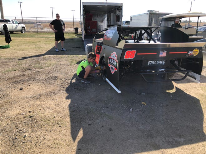 Driver Jack Kirchoff, Garden City, watches Saturday afternoon as his grandson, Cale Kirchoff, 10, tightens lug bolts on the elder Kirchoff's northern sport modified. They were preparing for the opening race Saturday night at RPM Speedway at the Ellis County Fair Grounds.