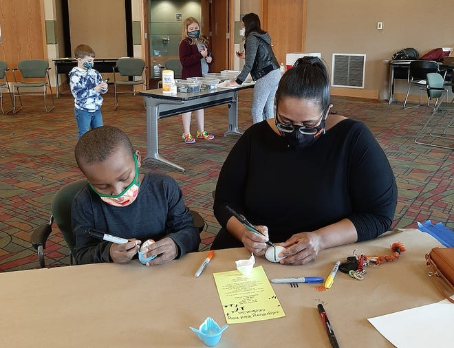 Kai Roundtree, left, and Greta Harrell decorate Easter eggs Saturday at the Freeport Public Library as part of a free event held with the Freeport Art Museum.