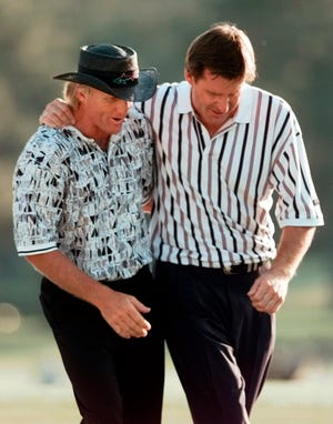 FILE - In this April 14, 1996, file photo, England's Nick Faldo, right, and Australia's Greg Norman walk off the 18th after Faldo won his third Masters golf tournament at Augusta National Golf Club in Augusta, Ga. This is the 25-year anniversary of the greatest collapse in major championship history.