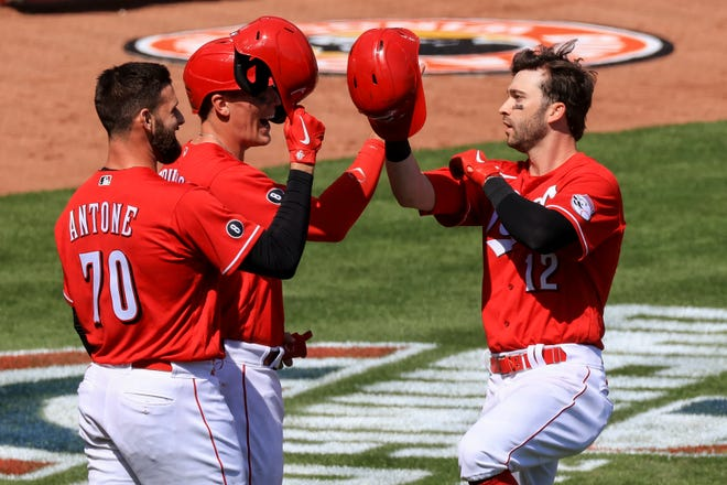Cincinnati Reds' Tejay Antone, left, and Tyler Stephenson, middle, celebrate the three-run home run hit by Tyler Naquin, right, during the sixth inning of a baseball game against the St. Louis Cardinals in Cincinnati, Sunday, April 4, 2021.