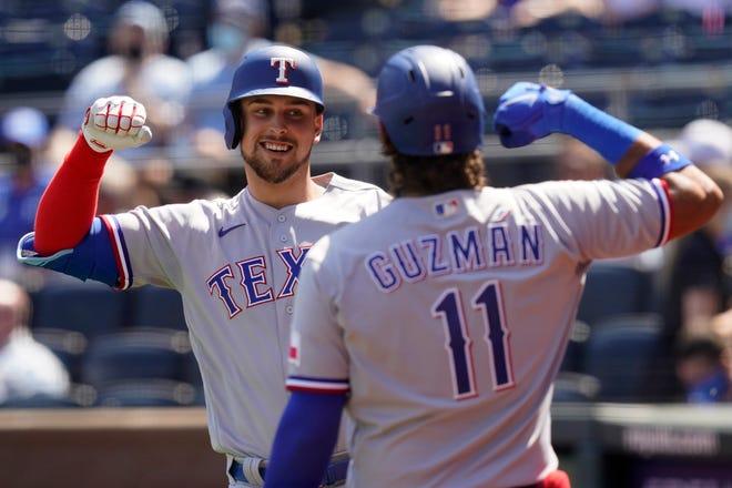 Texas Rangers Nate Lowe celebrates his three-run home run with teammate Ronald Guzman during the third inning of a baseball game at Kauffman Stadium in Kansas City, Mo., Sunday, April 4, 2021.