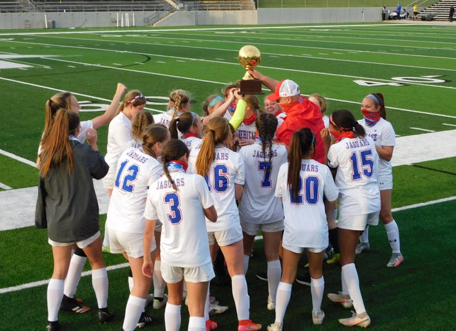 The Heritage High School girls' soccer team hoists more hardware following a victory over Carrollton Ranchview last week. The Jags advanced to the Class 4A Region I semifinals and were scheduled to take on Stephenville on Tuesday.