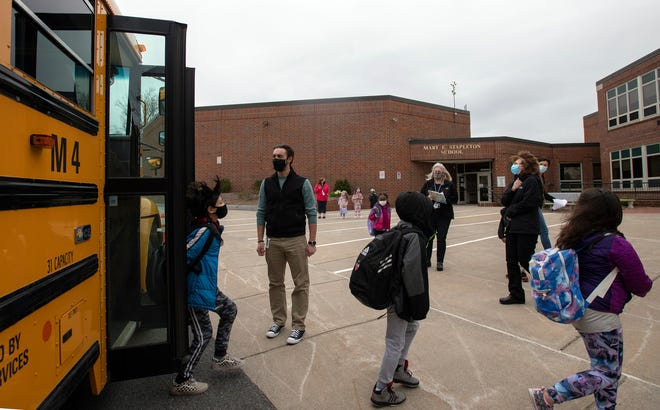 Technology Coach Luke Walton welcomes students off the bus as they arrive for the first full day of in-person classes at the Stapleton Elementary School, April 5, 2021.