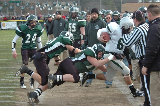 Marshfield's Jeffrey Wallace forces Duxbury quarterback Kane Haffey out of bounds during the 2010 Thanksgiving football game.