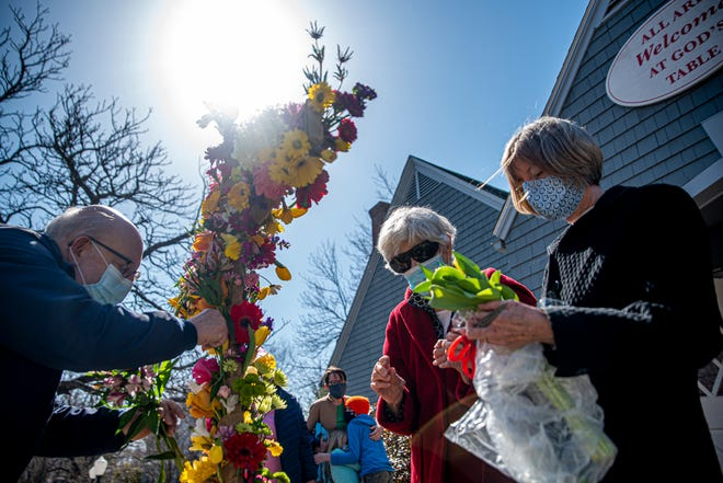 From the left, Mel Reisz, Marjorie Esau and Susan Washburn lay flowers on a cross as Marina Mails embraces her children, Eliza and Henry, outside St. George's Episcopal Church in York Harbor on Easter morning April 4, 2021.