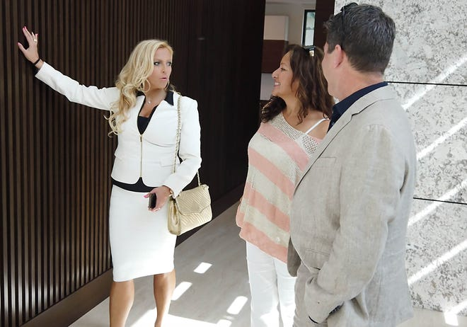 Kristina Krykhtin, Realtor with Signature One Luxury Estates in Boca Raton, shows a home to prospective buyers.