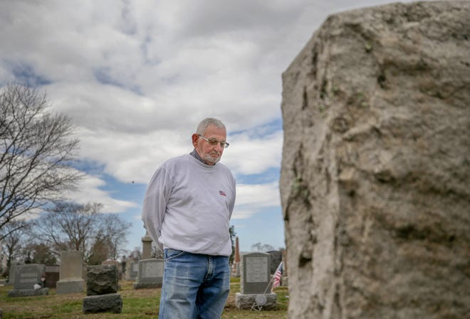 """Roger Messier stands before the grave of his wife, Lorraine, at Notre Dame Cemetery in Pawtucket. """"I always said, 'I'll be back,' and I gave her a kiss,"""" he said, recalling their final visit before COVID hit last March. """"I never knew that was the last time I would see her alive."""""""