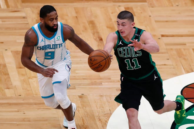 Payton Pritchard (11) passes in front of the Hornets' Brad Wanamaker during the first half of a Sunday's game in Boston.
