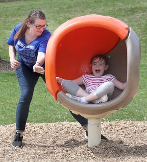 Morgan Choffin plays with her daughter, Emerson Choffin, at Veterans Park in Plain Township last week. The township is asking voters to approve a 1-mill parks levy in May.
