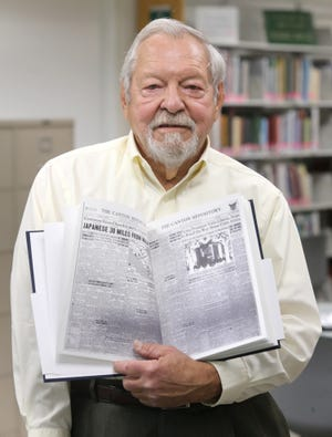 Don Stock holds a book Monday that his granddaughter Jessica Morford made for him that featured 80 front pages of The Canton Repository for his 80th birthday. He is shown with the front page from the day he was born. The Stark County District Library assisted with the birthday present.