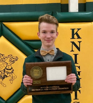 St. Mary's sophomore CJ Surprenant spent the basketball season broadcasting the Knights girls' and boys' home games on Facebook Live.  CJis pictured following the boys' final home game, on March 24, with the Sub-Section Championship plaque they won that night.