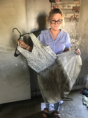 Megan Brown holds her wedding dress covered in soot from the fire.
