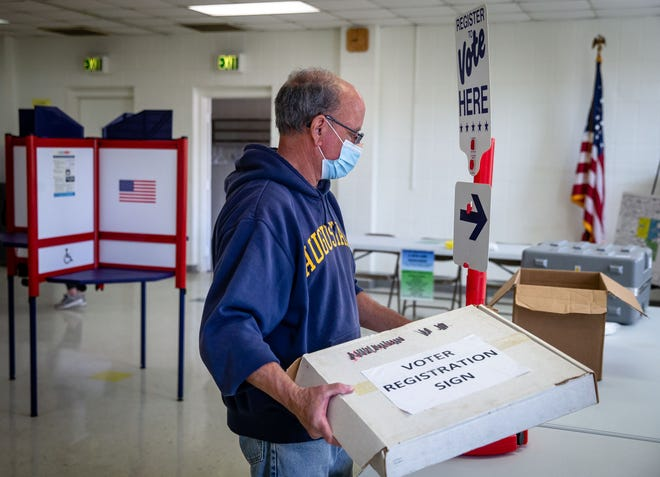 Election worker Jim Schlouch prepares the signage for the same day voter registration table as they set up the polling place for the consolidated election at the Jerome Civic Center Monday.