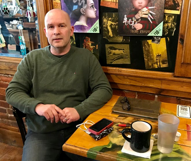 """Local podcast creator Daniel Williams talks about his show """"The Midnite Hour with Tom Bobbajobski"""" in Raven Café in Port Huron, Mich., Friday, March 19, 2021. (Bryce Airgood/The Times Herald via AP)"""