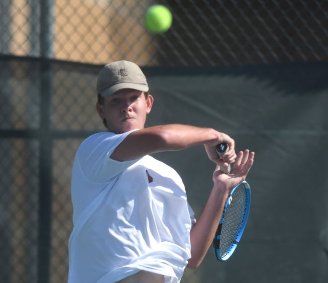 New Hanover Alan Dimock tennis player returns a shot at Hoggard in Wilmington, N.C., Monday, April 5, 2021.    [MATT BORN/STARNEWS]
